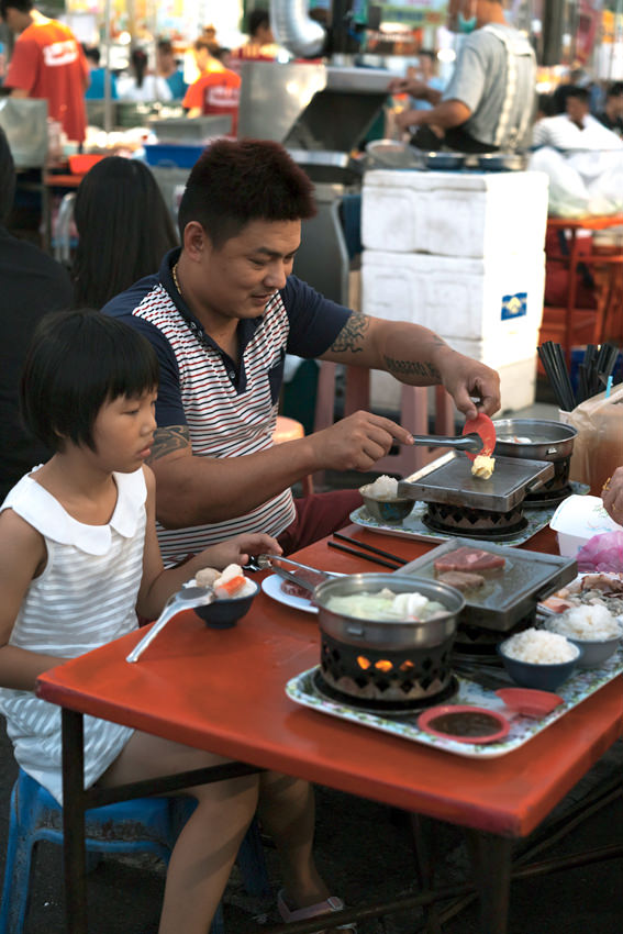 Father and daughter in night market