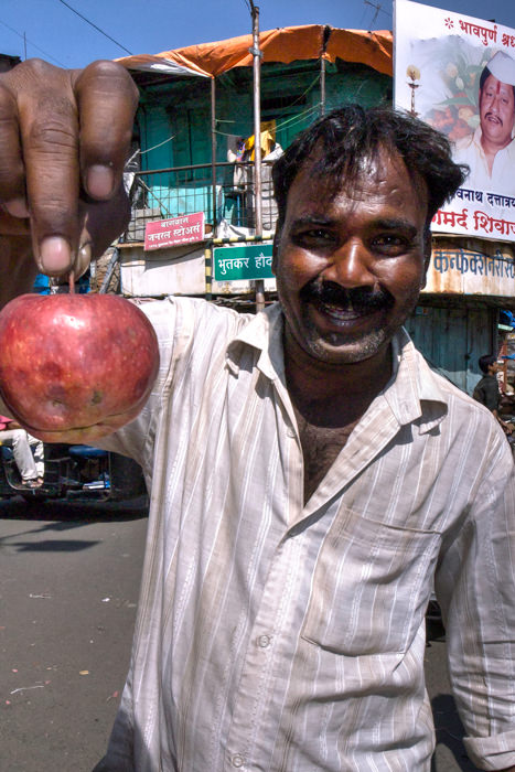 Man Pinching The Stem Of An Apple (India)