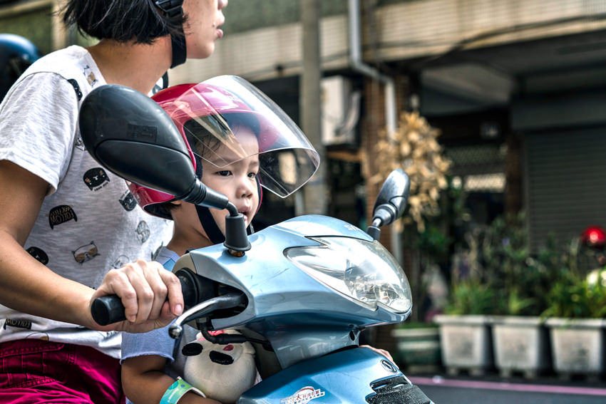 Kid on motorbike with mother