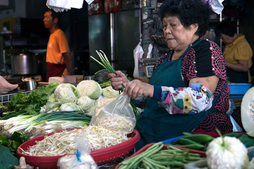 Older woman selling vegetables