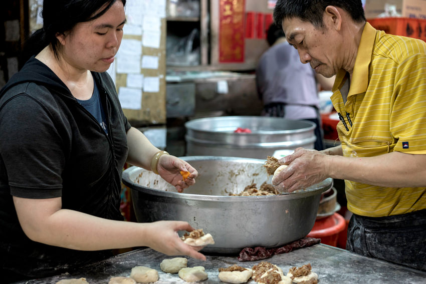 Man and woman making meat buns