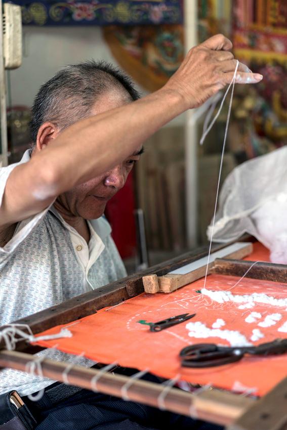 のれんを縫う男