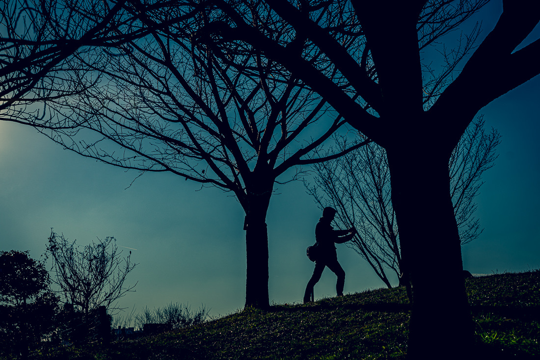 Silhouetted man taking photos in Saigoyama park