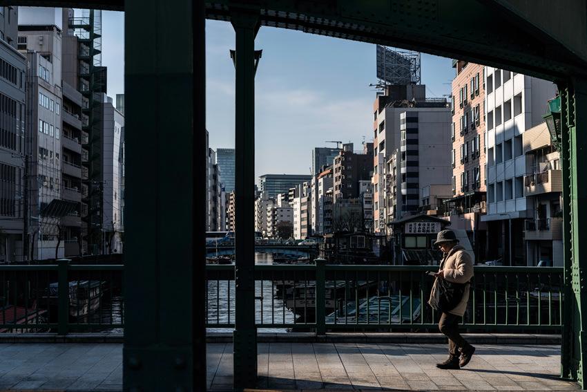Hatted man walking on iron bridge