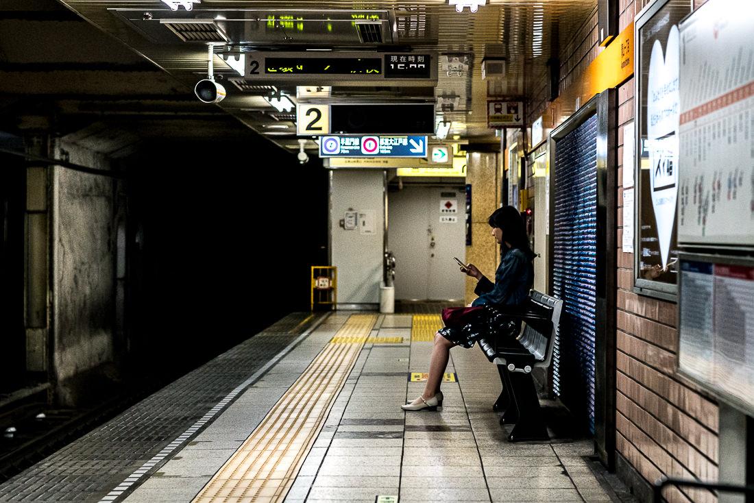 Woman sitting on bench on platform