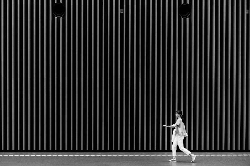 高い壁の前を歩く女