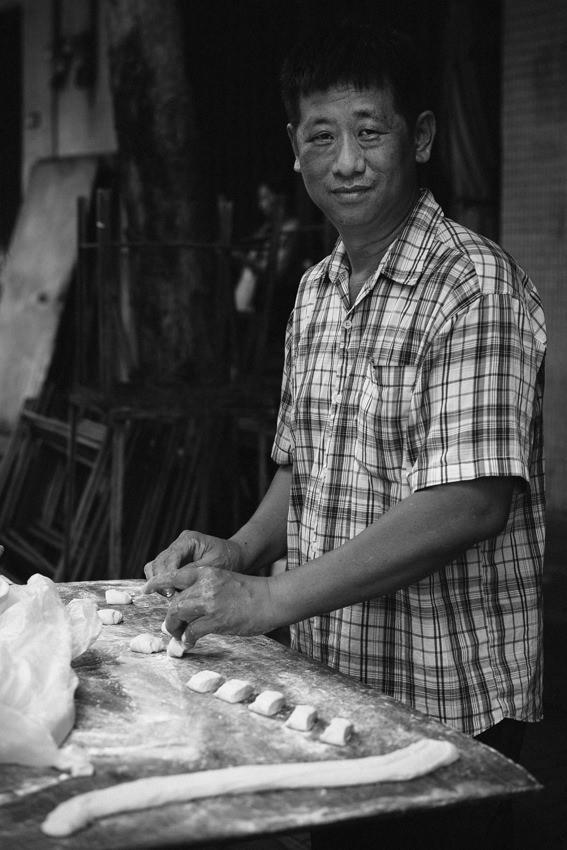 Man cutting dough into pieces