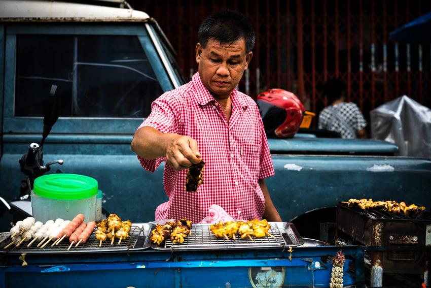 Man roasting skewered meat