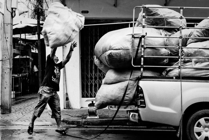 Man tossing big bag onto car