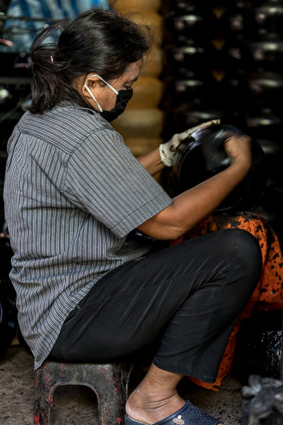 Woman painting alms bowls