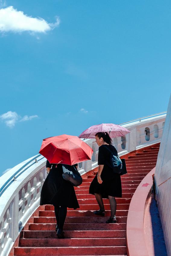Women climbing red stairway in Wat Saket