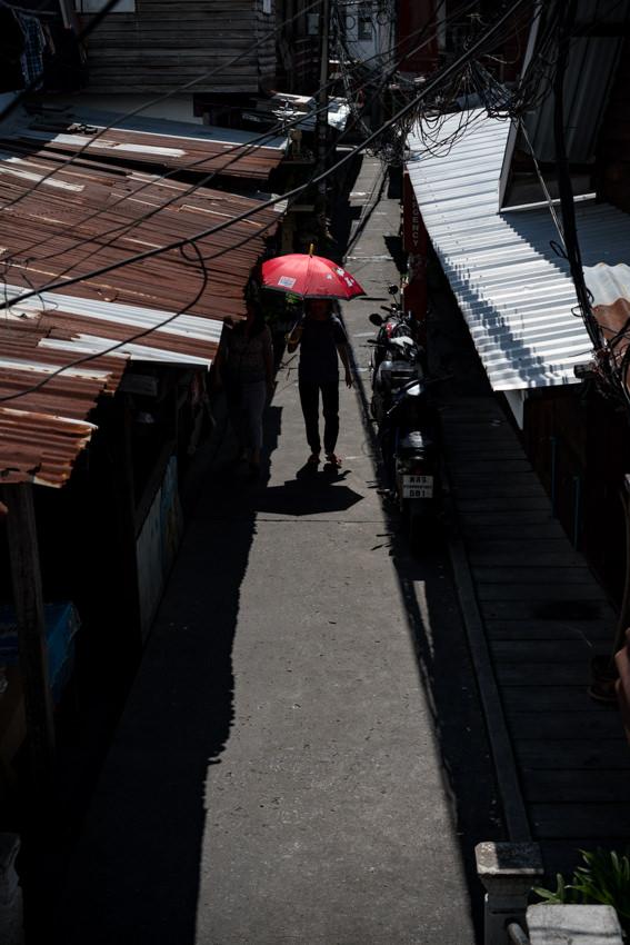 Figure with red umbrella walking between zinc roofs