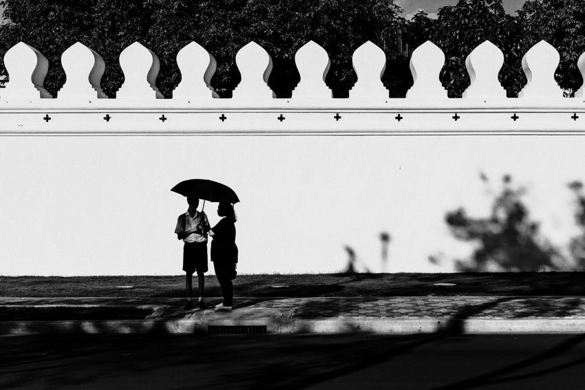 Silhouettes standing under same umbrella