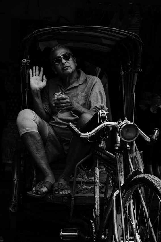 Shade-wearing man sitting on bike taxi