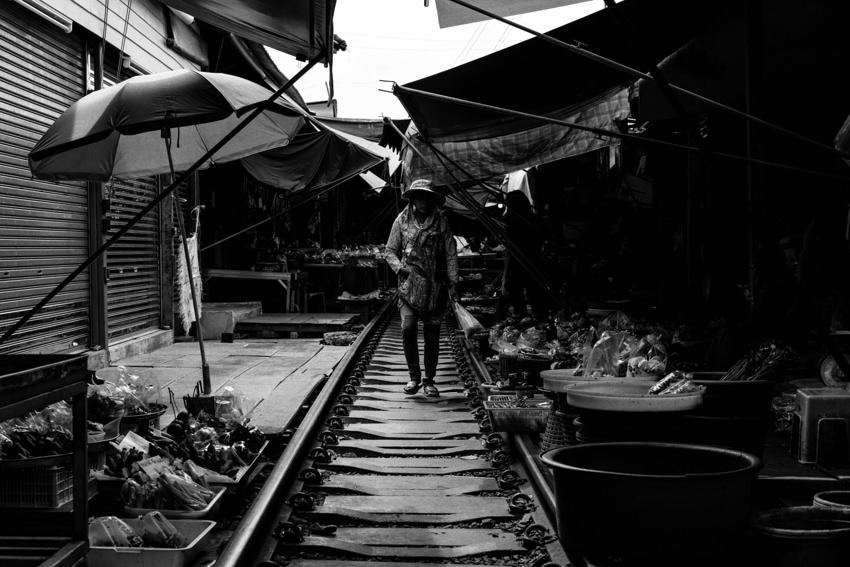 ビニール袋を片手に線路の上を歩く女