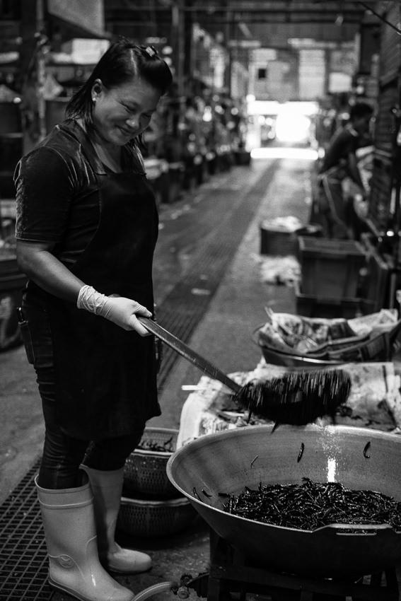 大きな鍋で唐辛子を炒めていた女性