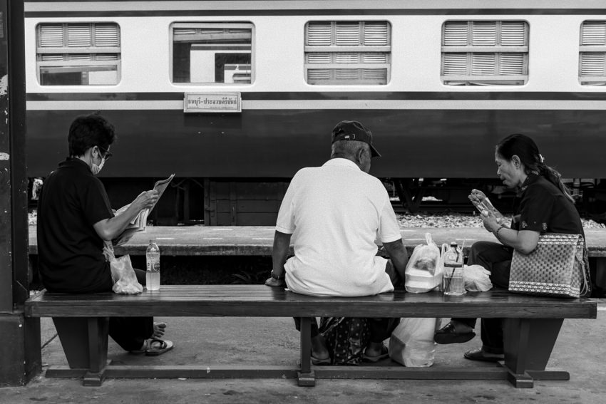 Three persons sitting on same bench on platfrom