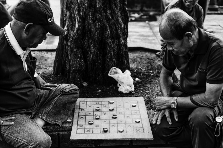 Men playing game on sidewalk