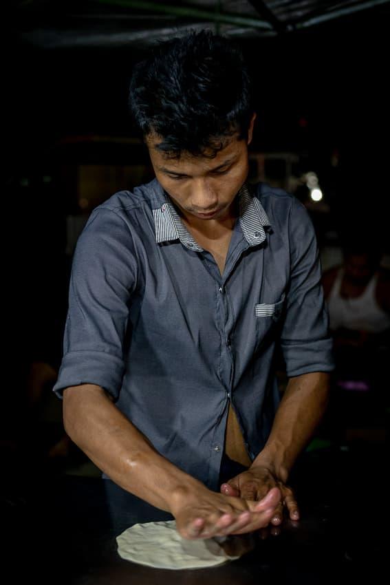 Man flattening dough into disk
