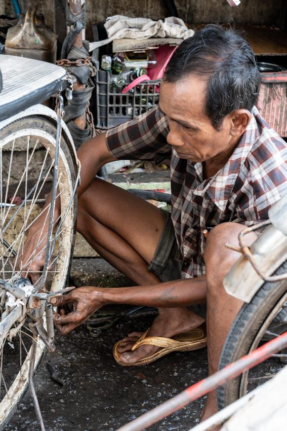 自転車タクシーを修理する男