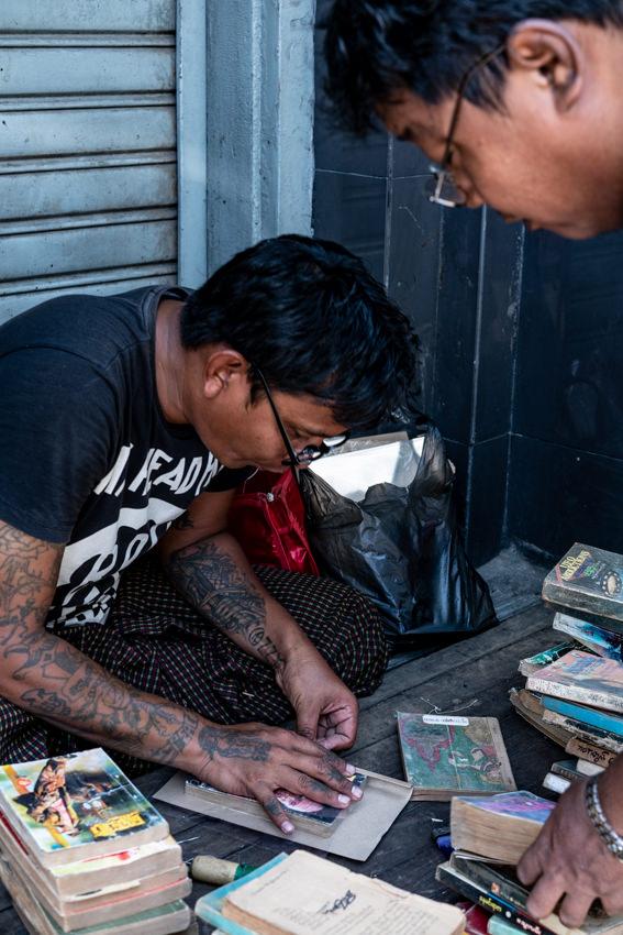 歩道の端で古本の修理をする男