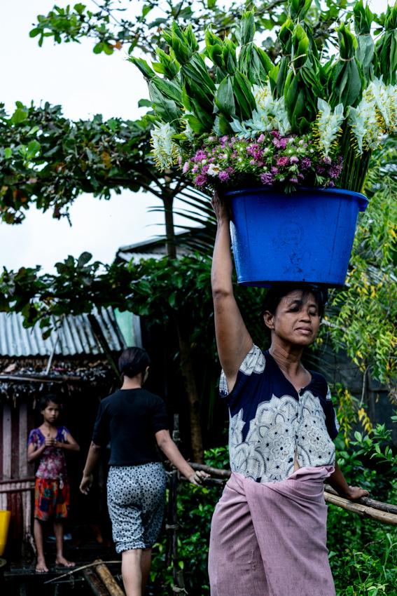 頭上に載せて花を運んでいた女性