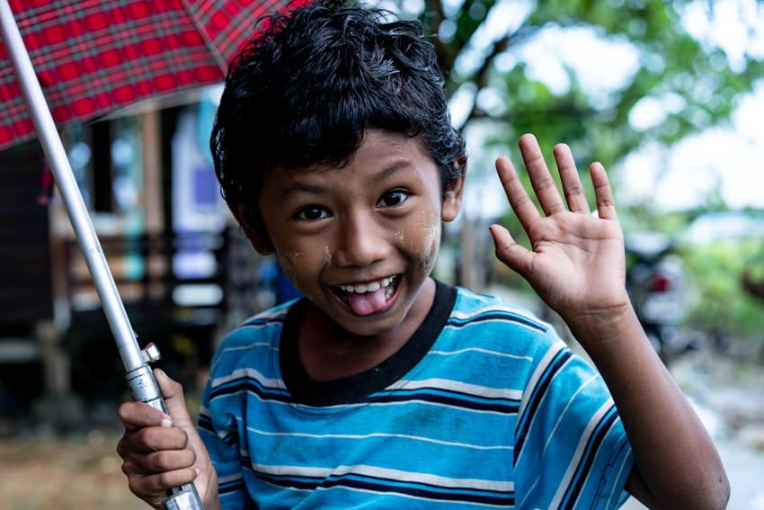 Boy smiling while holding umbrella