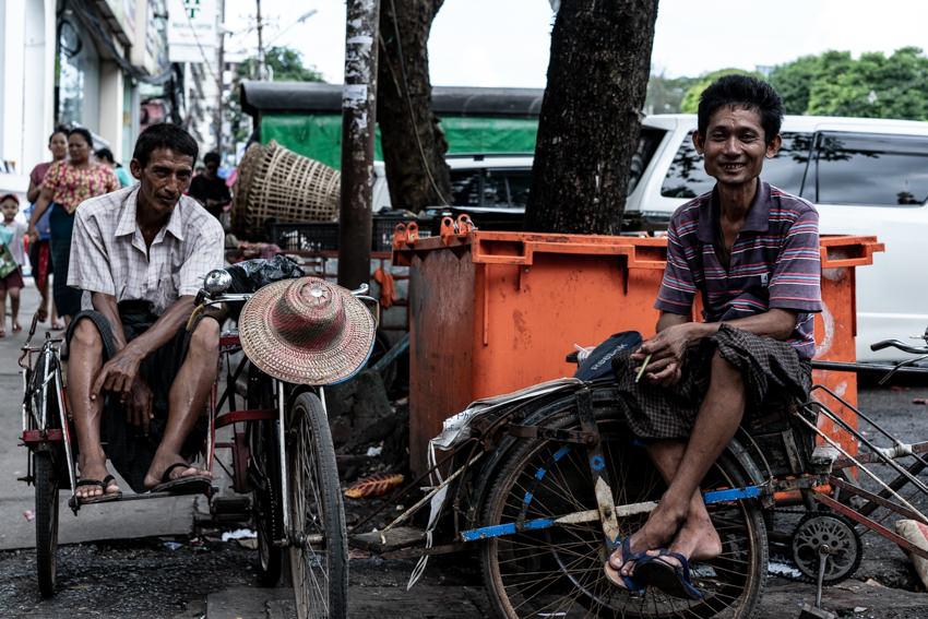 Rickshaw men sat on saddle of vehicle