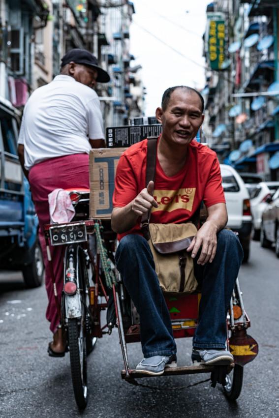 自転車タクシーの座席で親指を立てた男