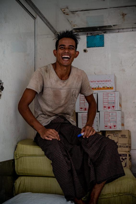 トラックの荷台で笑う男