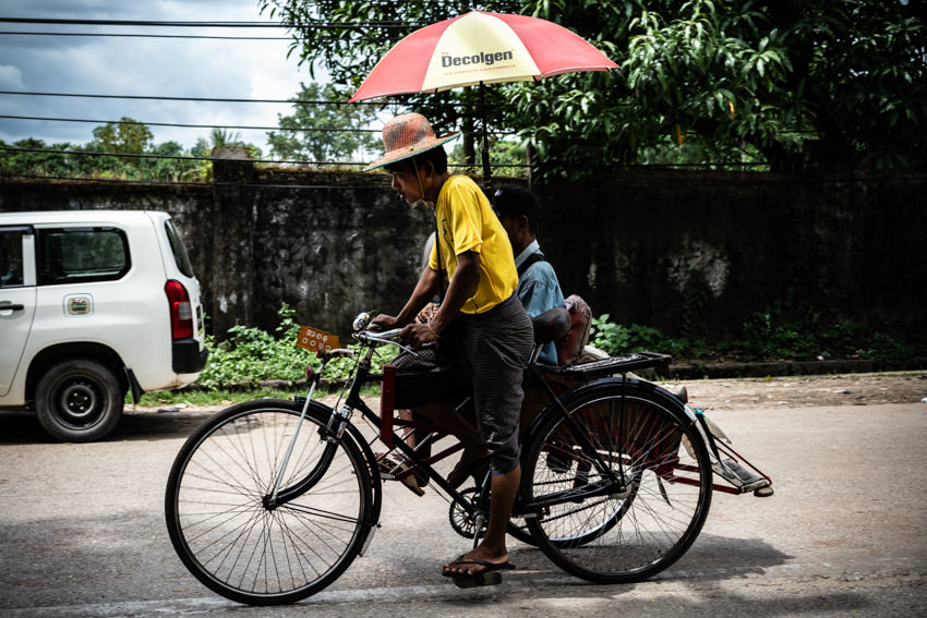 Pedicab with umbrella passing by