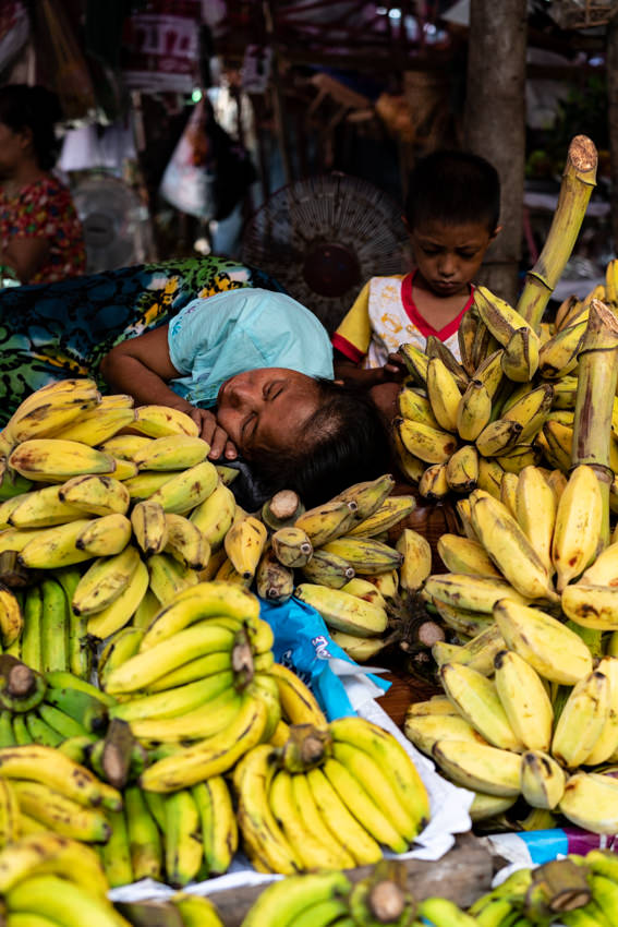 Mother sleeping on the other side of the pile of bananas