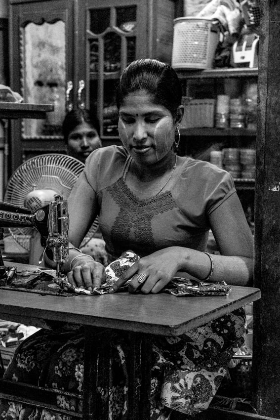 Woman sewing in dim shop