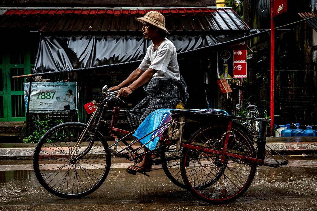 Hatted man pedaling pedicab called Saiq-ka