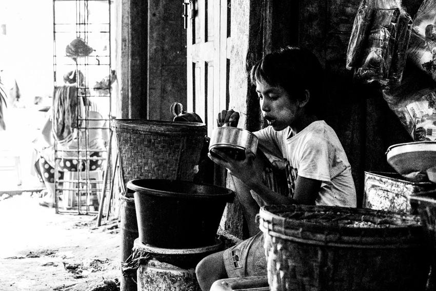 市場の片隅でお弁当を食べていた男の子