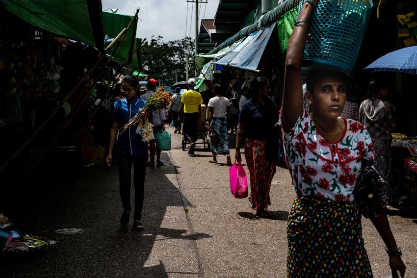 頭に買い物バッグを載せて歩く女性