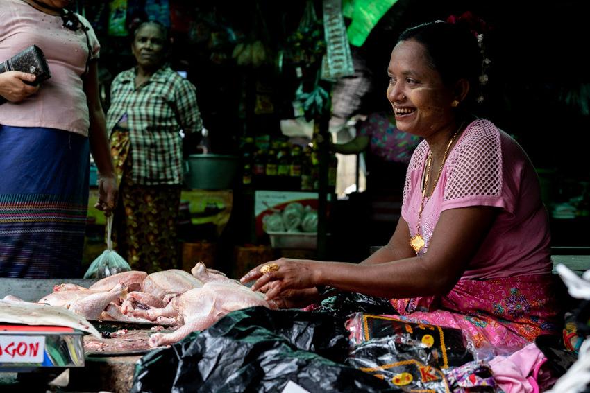 苦笑しながら鶏肉を売る女性