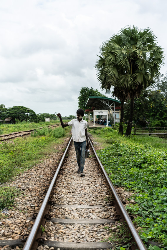 Young man walking on railway track with lunch box