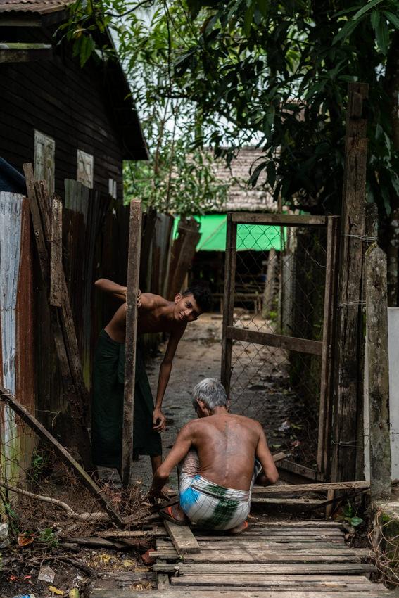 門を修理する二人の男