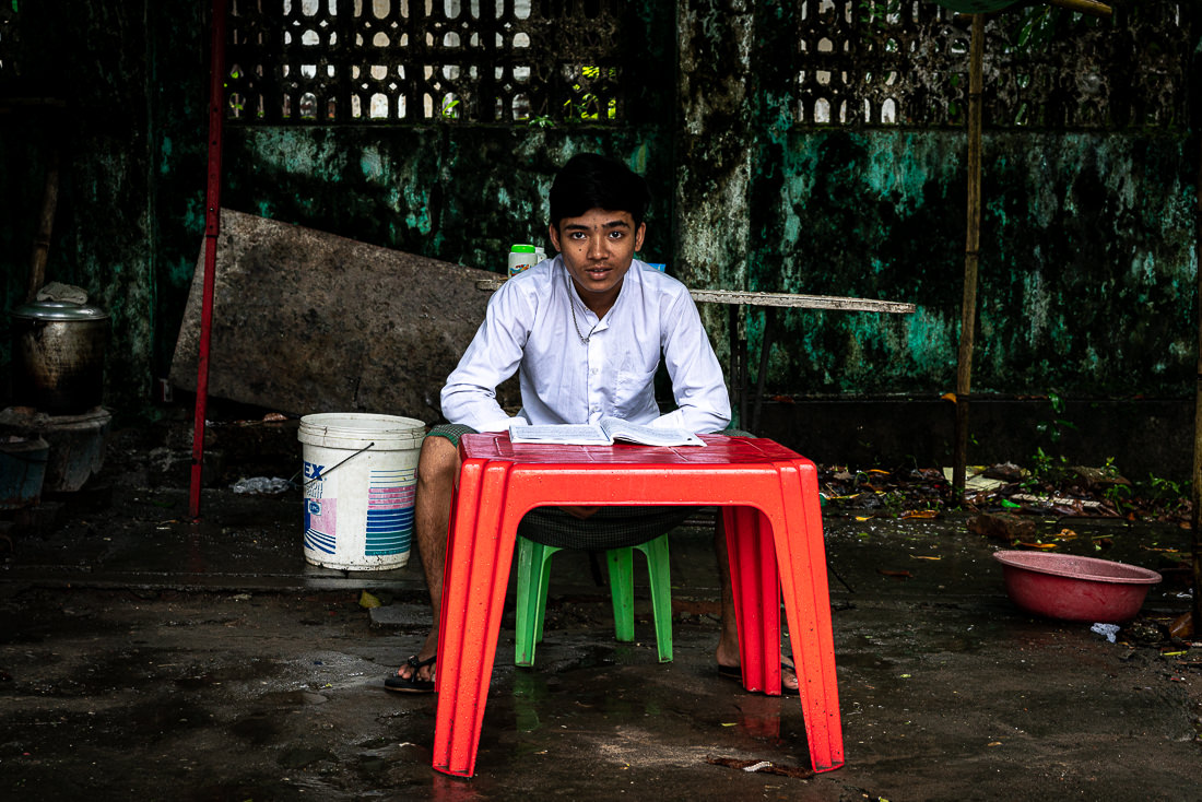赤いテーブルで勉強する男子学生