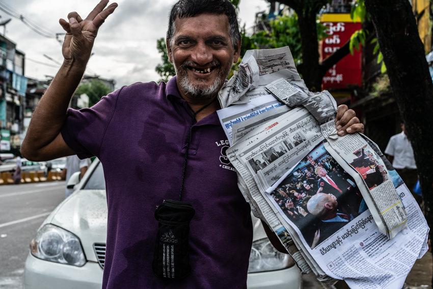 路上で新聞を売っていた男