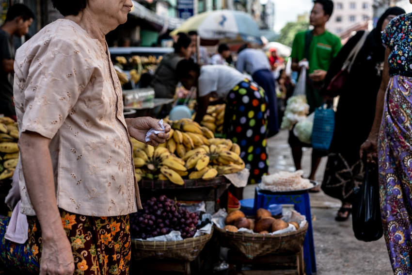Older woman walking in front of fruits