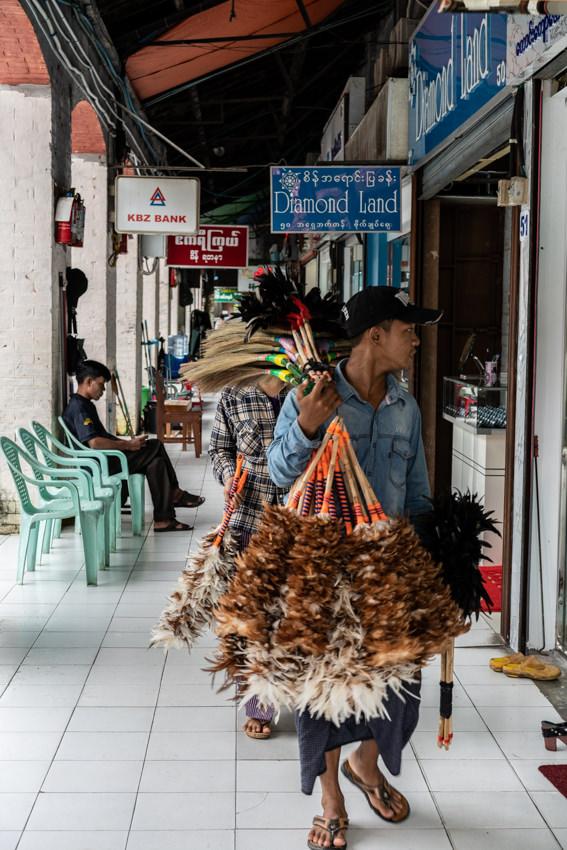 Man peddling various brooms