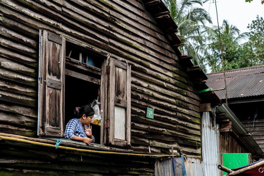 2階の窓辺に立つ女