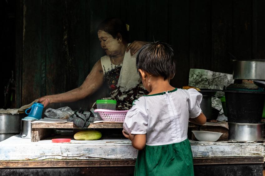 惣菜屋で買い物をする制服姿の女の子