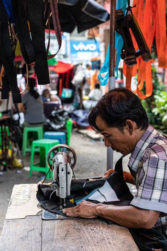 ミシンを使って縫製する男