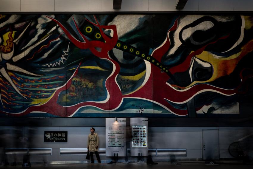 岡本太郎作の大きな壁画の下に立ち止まる男