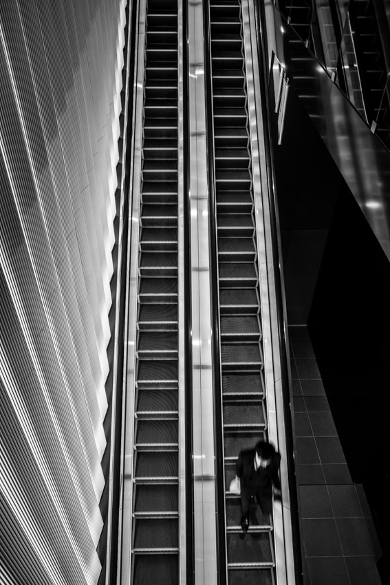 Man riding down an escalator