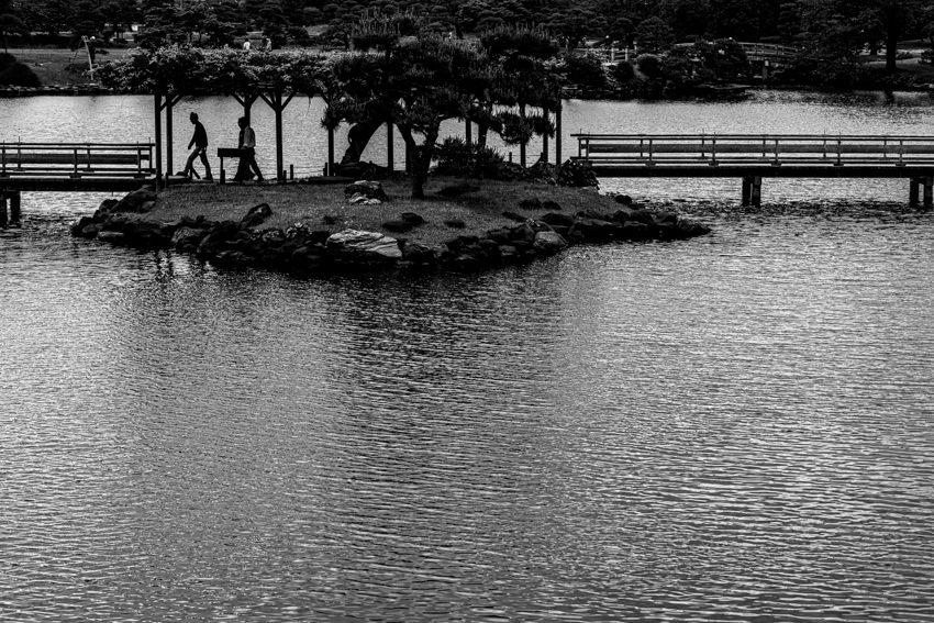 潮入の池に浮かぶ小島の上を歩くシルエット