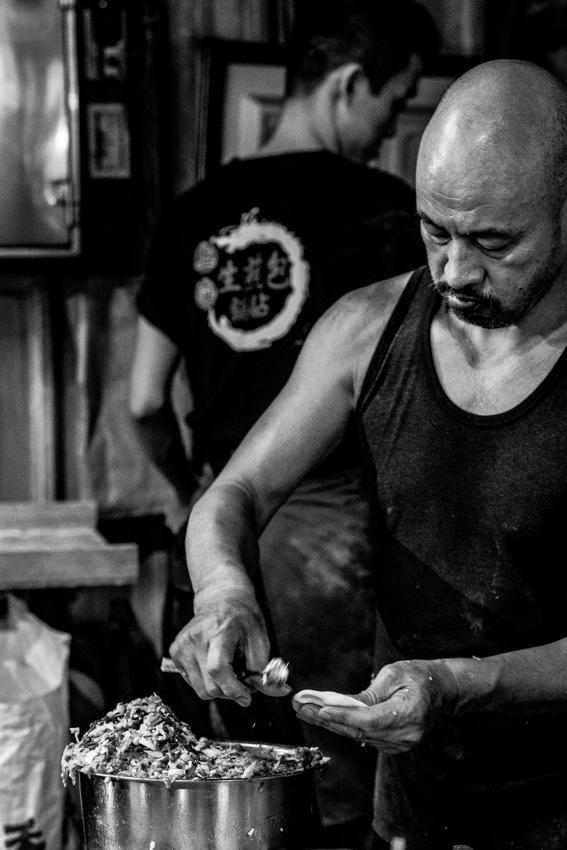 Man making Shengjian Bao one after another
